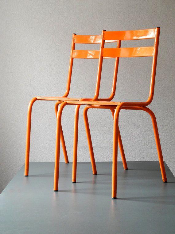 Two original TOLIX bistro chairs with original orange color .