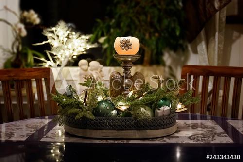 Ein Gesteck mit Kerze und grünen Tannenzweigen schmückt zur .