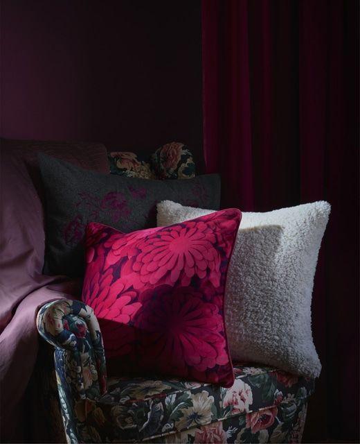 Gemusterte Kissen auf einem Stuhl mit dunklem Blumenmuster, u. ein .