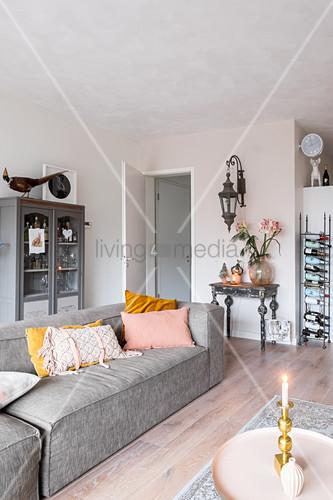 Graues Sofa vor Vitrinenschrank in … – Bild kaufen – 12478375 .