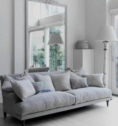 ein großer Spiegel und ein graues Sofa, ein weißer Teppich .