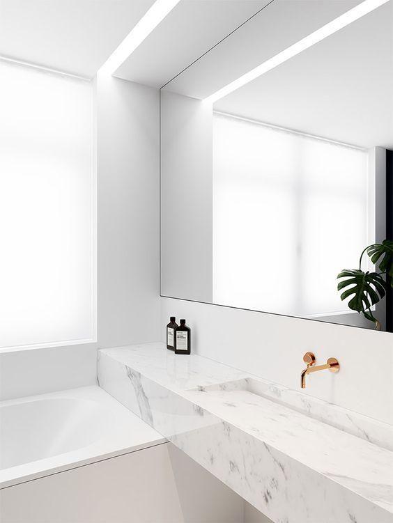 Kleines weißes Marmor modernes Badezimmer mit Spiegel und Zähler .
