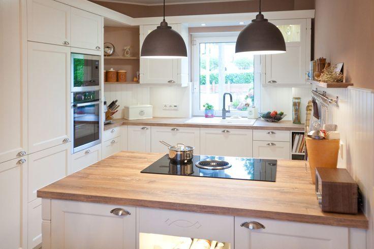 Moderne Landhausküche in weiß von Häcker Küchen mit Kochinsel .