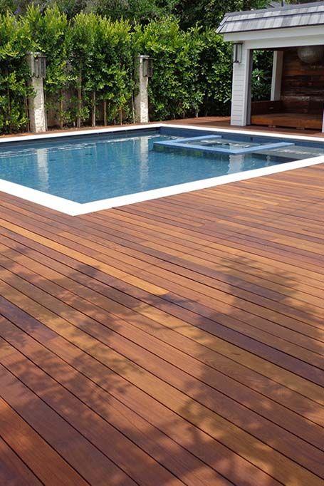 Trex pool deck. Brown decking with travertine pool bullnose .