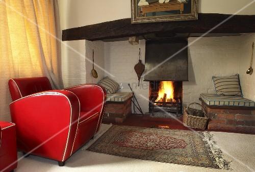 Ein roter Ledersessel vor einem Kamin … – Bild kaufen – 11000053 .