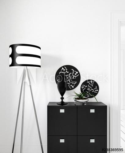 Schwarze Kommode vor weißer Wand mit Stehlampe und Deko - Buy this .