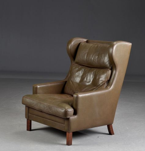 Taupe colored leather high armchair / lounge chair, wingback chair .