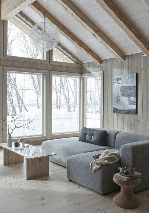 Snowy cabin with comfy cuddle-sort-of-couches and large windows to .