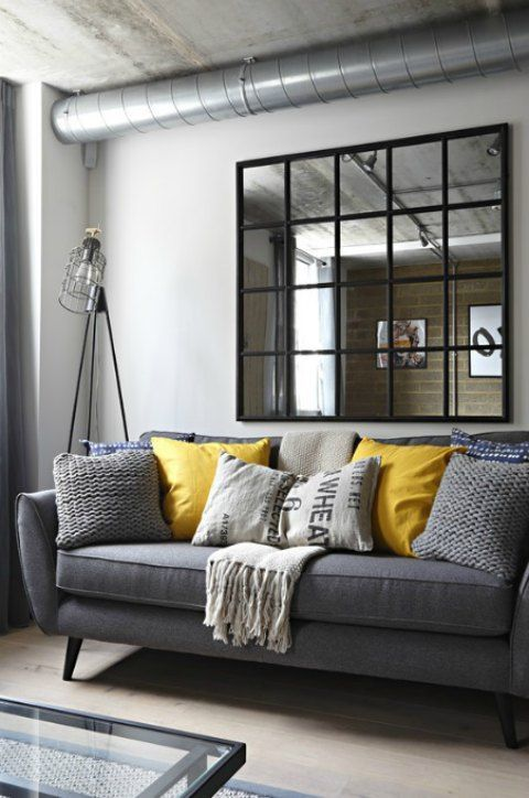 A gray industrial living room with a gray sofa and yellow pillows .